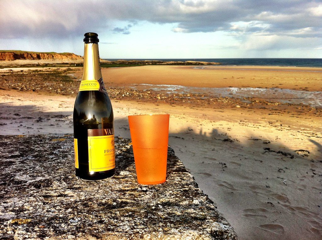 Bottle of Prosecco on a beach © James West