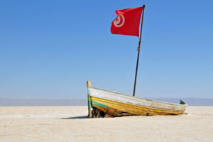 Boat on a dry beach with the Tunisian flag flying © Dennis Jarvis