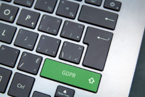 Computer keyboard with green GDPR button. www.comparitech.com/